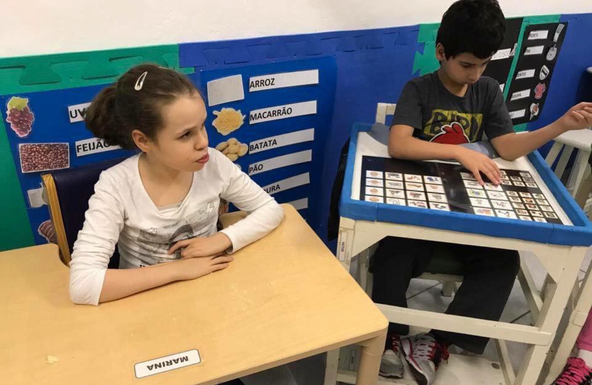 duas crianças sentadas em uma mesa escolar adaptada dentro de uma sala de aula