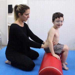 fisioterapeuta segurando o quadril de uma criança sentada no rolo de fisioterapia