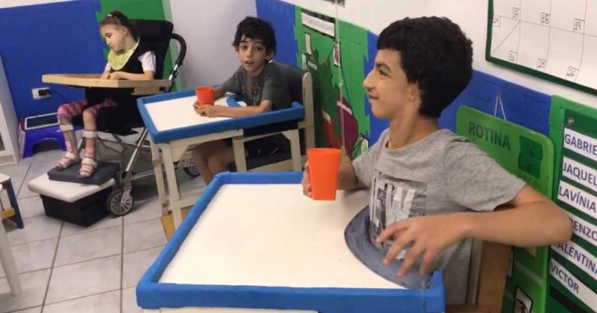 3 crianças sentadas em sala de aula prestando atenção na professora